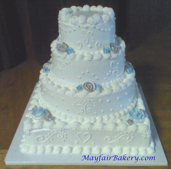 Four tier silver and blue wedding cake with square base and round tiers.