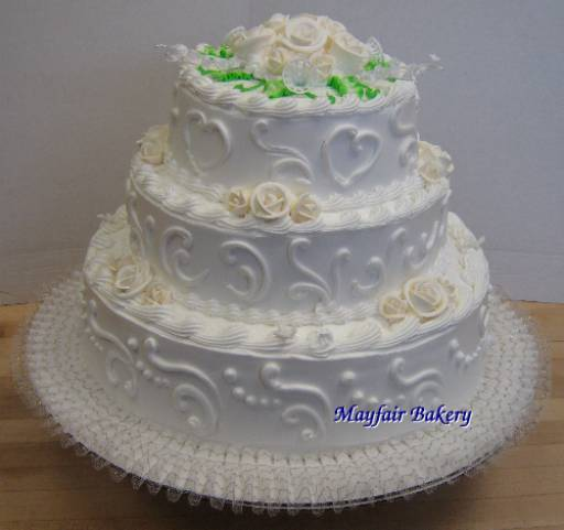 Three tier white wedding cake with scrollwork